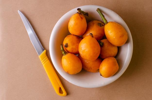 Loquats frais sur une assiette blanche et un couteau sur beige