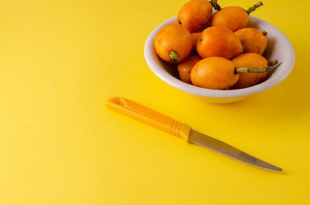 Loquats frais mûrs sur plaque blanche et nkife sur jaune