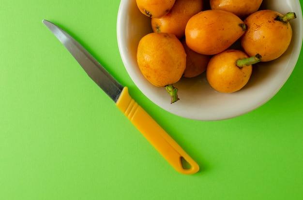 Loquats frais mûrs sur plaque blanche et nkife sur vert