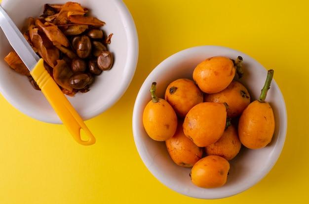 Loquats frais et pelés dans un bol blanc et un couteau sur fond jaune