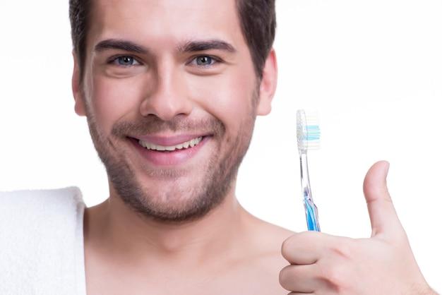 à â¡lose-up portrait d'un jeune homme heureux avec une brosse à dents - isolé sur blanc.