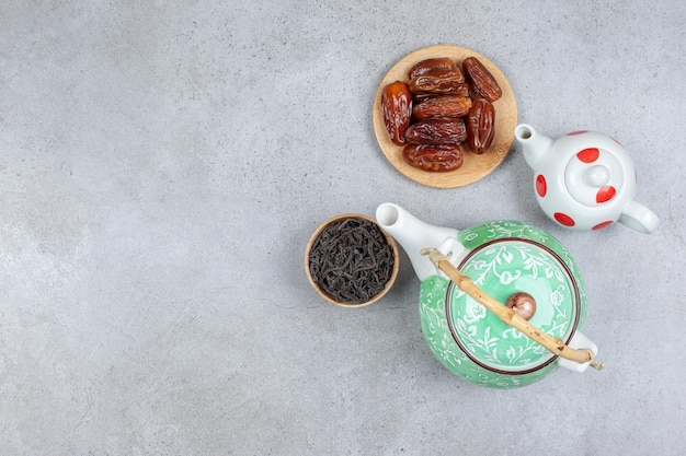 Un lot de deux théières, un petit bol de feuilles de thé et une poignée de dattes sur fond de marbre.