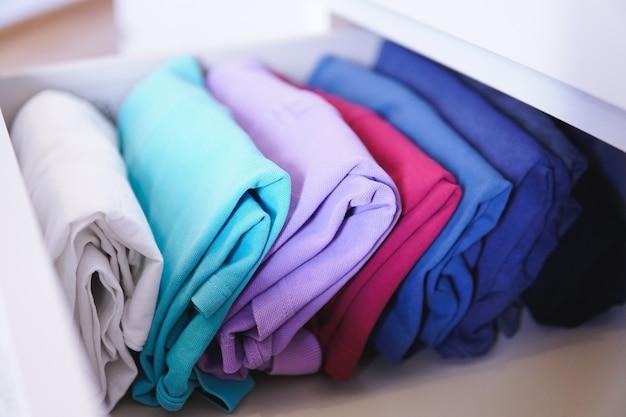 Lot de différents vêtements pliés parfaitement disposés dans un placard - concept de méthode marie kondo konmari