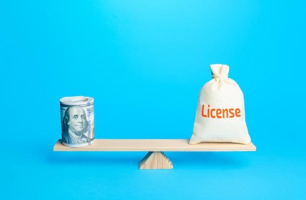 Lot de dollars et un sac avec word licence sur les balances estimation de la valeur des droits d'auteur et des brevets