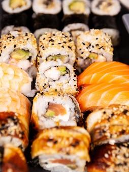 Lot mélanger une variété de rouleaux de sushi sur fond de pierre noire en photo de studio