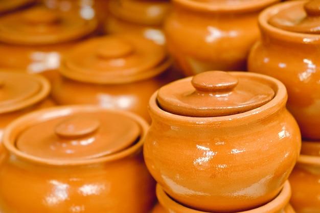 Lot de mêmes pots en terre cuite brune en céramique avec couvercles en gros plan. petits pots en argile au marché.