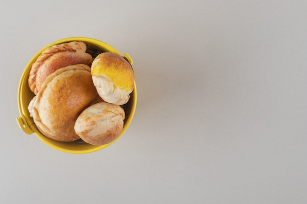 Lot de petits pains dans un seau sur fond de marbre.