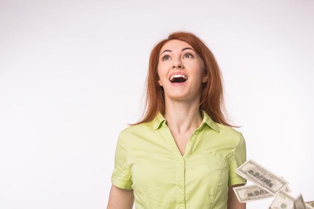 Loterie, concept de réussite financière. excité femme debout sous la pluie d'argent sur blanc.