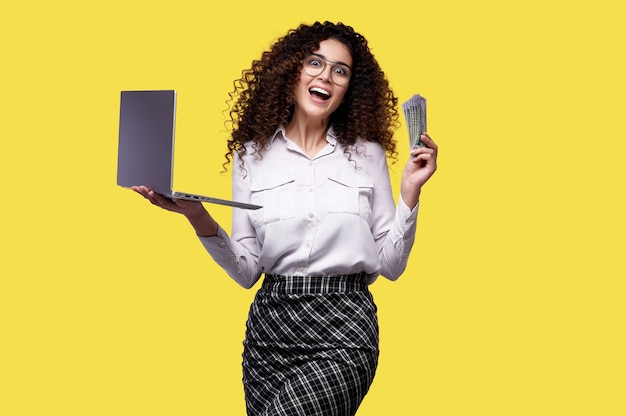 Loterie en ligne. business girl holding ordinateur portable et de l'argent sur le mur jaune