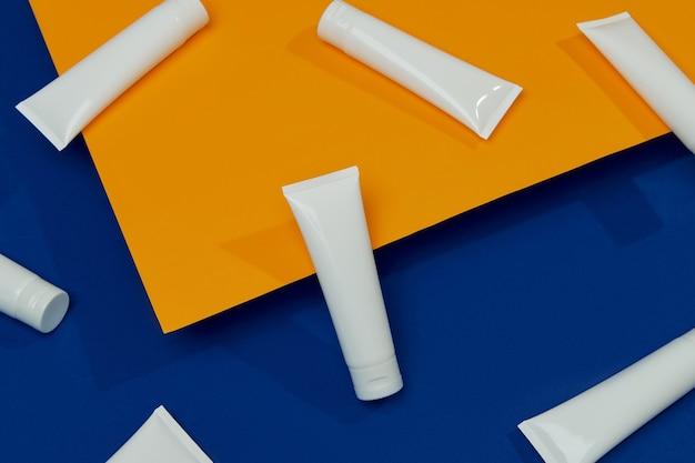 Lotion ou crème sur fond orange et bleu visage soins de beauté soins du corps