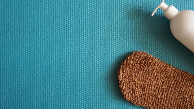 Lotion, éponge de douche sur fond bleu. concept de peau saine et belle.