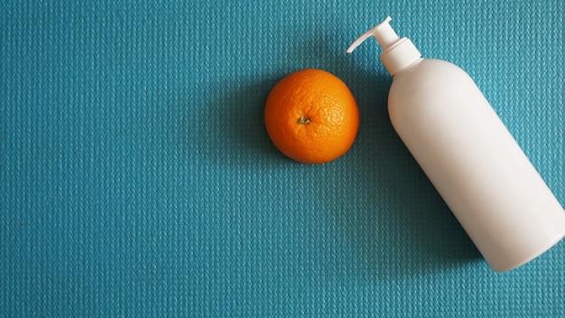 Lotion et fruit orange - concept anti-cellulite sur fond bleu