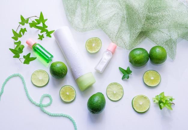 Lotion pour le visage et tonique en bouteilles, tranches de citron vert, feuilles vertes - en utilisant l'essence d'agrumes pour le concept de produits cosmétiques