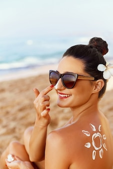 Lotion solaire belle femme appliquant sur le visage