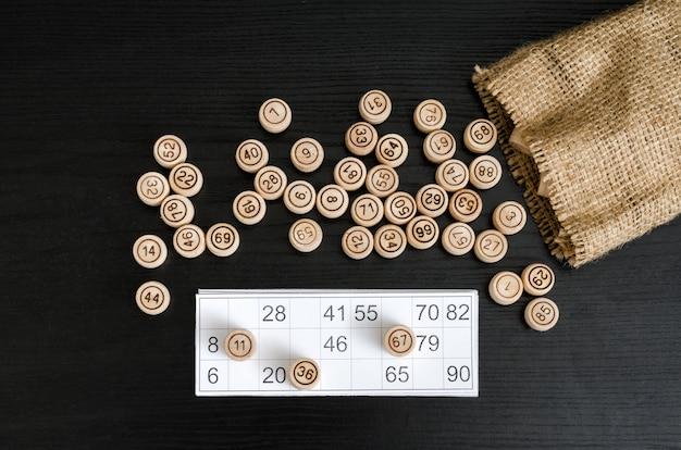 Loto en bois, carte pour gibier et sac sur une table noire. directement au-dessus.