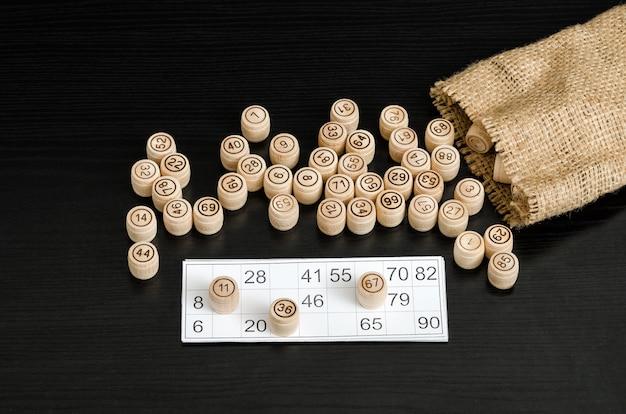 Loto en bois, carte pour gibier et sac sur une table noire.