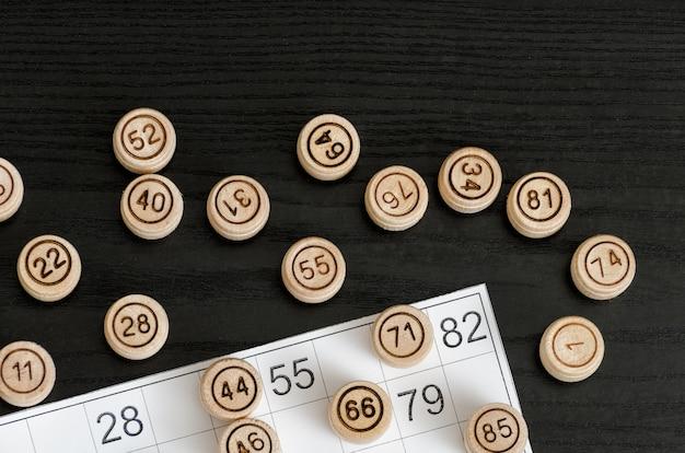 Loto en bois et carte pour jouer sur une table noire