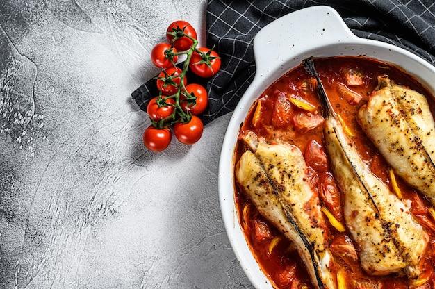 La lotte cuite aux tomates dans un plat allant au four. fond noir