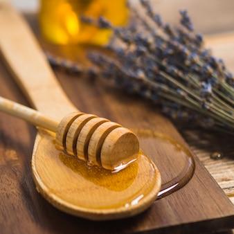 Louche de miel sur une cuillère en bois avec du miel sur une planche à découper