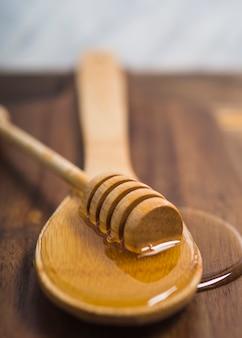 Louche de miel sur une cuillère en bois avec du miel