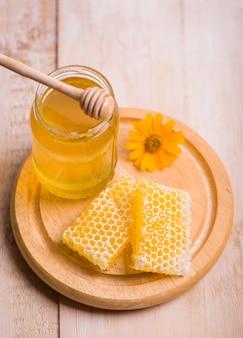 Louche de miel sur le fond en nid d'abeille.