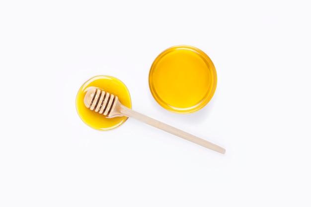 Louche de miel et miel dans un bol en verre sur fond gris clair. taches de miel. voir en haut