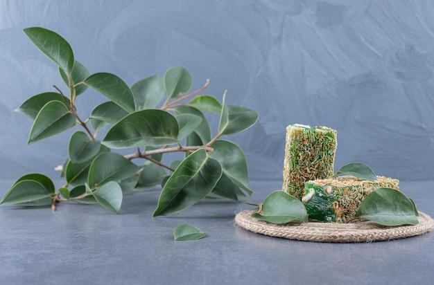 Loukoum rahat lokum aux noisettes et feuilles décoratives sur fond gris.