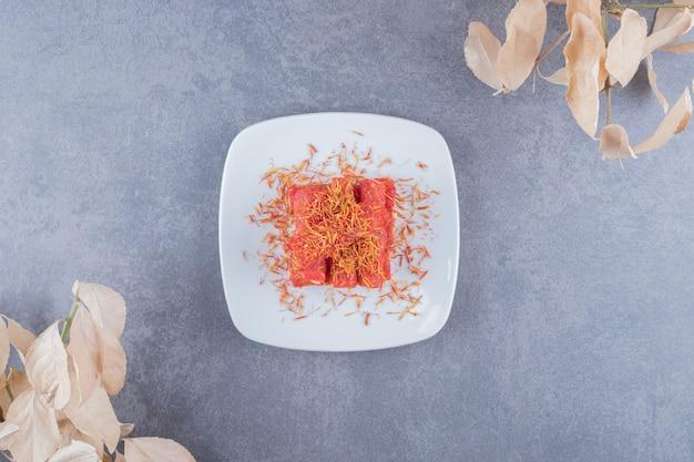 Loukoum rahat lokum aux pistaches sur plaque blanche avec des feuilles séchées.