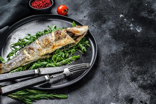 Loup de mer au four avec roquette sur table noire.