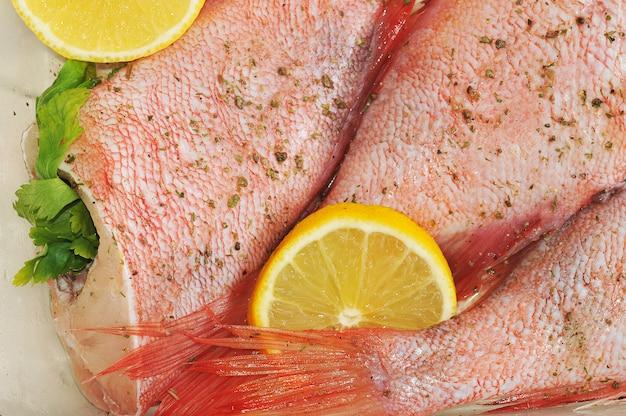 Loup de mer cru farci de persil et de citron dans un plat en verre sur une surface en bois