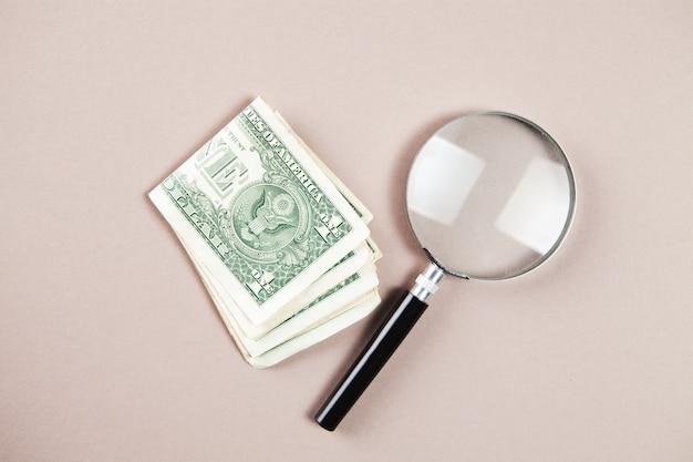 Loupe et argent sur une surface blanche