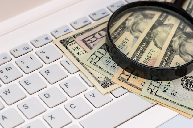 Loupe et billets d'un dollar sur ordinateur portable