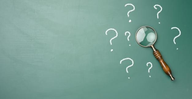 Loupe en bois et points d'interrogation dessinés à la craie blanche sur un tableau vert. le concept de trouver des solutions, vraies ou fausses. réponses aux questions