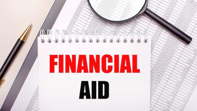 Loupe de bureau, rapports, stylo et bloc-notes avec texte aide financière. concept d'entreprise