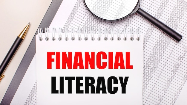 Loupe de bureau, rapports, stylo et bloc-notes avec texte littératie financière. concept d'entreprise