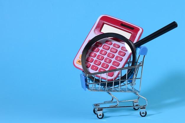 Loupe et calculatrice en plastique rose dans un chariot rose miniature sur fond bleu. concept de planification budgétaire, comptage des économies, contrôle des coûts
