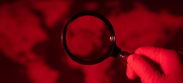 Loupe sur la carte rouge tonique, concept de pandémie mondiale