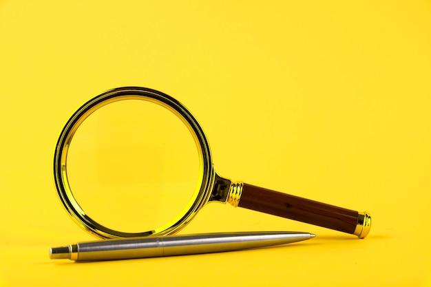 Une loupe dans un cadre doré et un stylo sur fond jaune