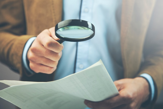 Loupe et document de main d'homme d'affaires