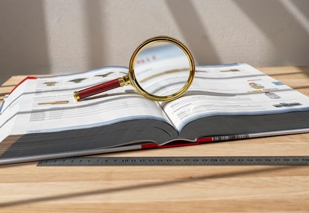 Loupe dorée sur un livre technique épais ouvert sur le concept de bureau d'étude scientifique et de recherche...