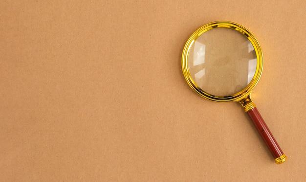 Loupe dorée sur l'outil de recherche de fond de carton brun avec fond