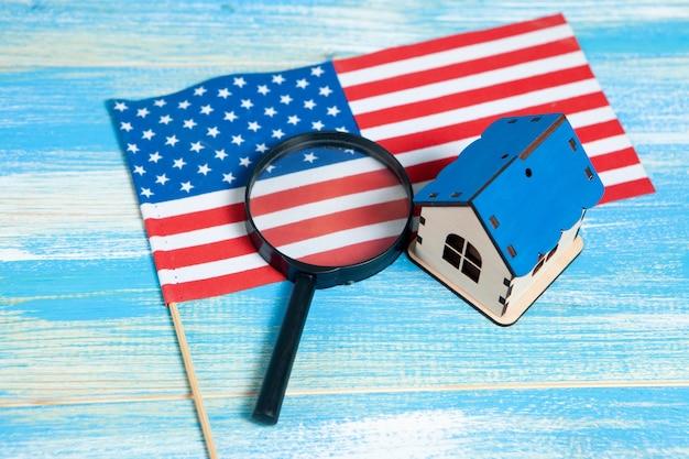 Loupe, drapeau américain et maison. concept de recherche à domicile. inspection de la maison sur une table bleue