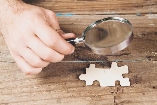 La loupe examine les pièces du puzzle