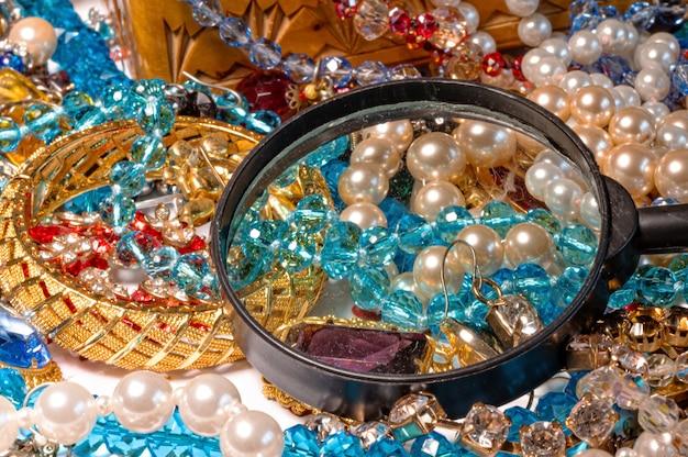 Loupe sur fond de bijoux brillants multicolores, le concept de prospérité, gros plan