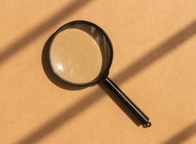 Loupe sur fond de carton marron avec lumière du jour et ombres. outil de recherche.