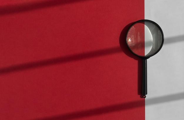 Loupe sur fond rouge avec outil de recherche de lumière du jour sur bannière avec espace de copie