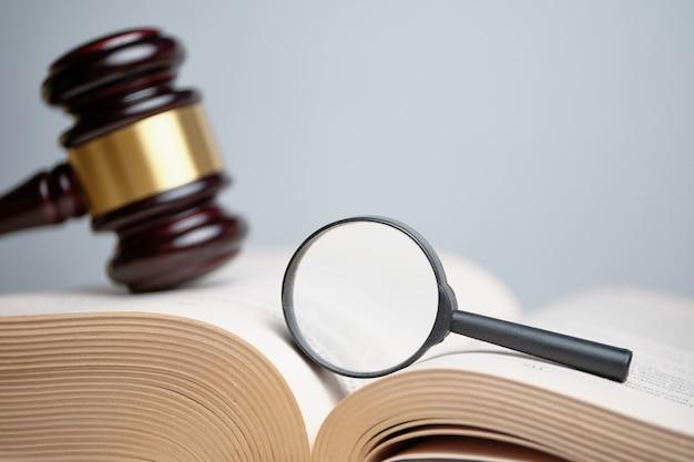 La loupe sur le livre à côté du marteau du juge
