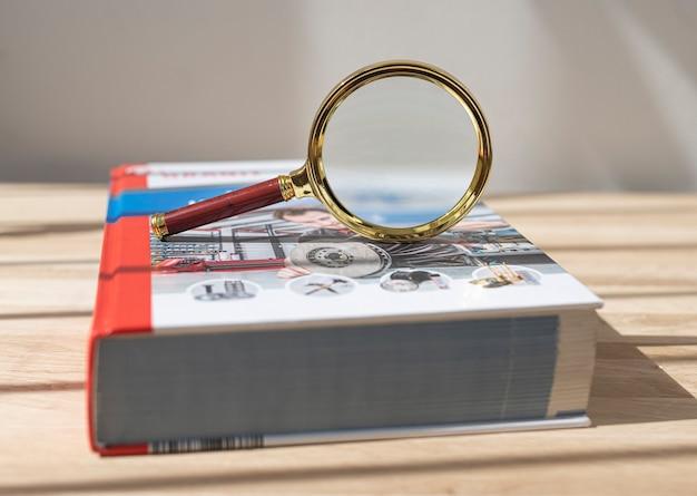 Loupe sur un livre technique épais fermé à couverture rigide sur un bureau en bois concept de science...