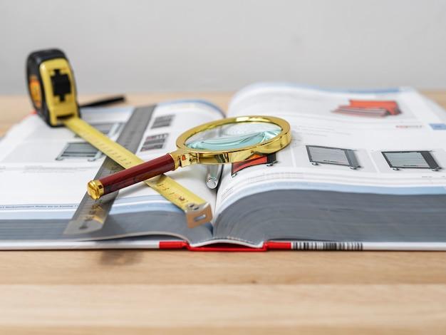 Loupe sur livre technique ouvert sur le concept de gros plan de bureau d'étude et de recherche scientifiques