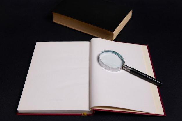 Une loupe, une loupe, une loupe sur un livre ouvert en couverture rouge rigide, isolée sur fond noir avec un espace pour le texte. concept de la journée des enseignants, connaissances, littérature, lecture, érudition